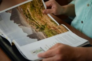 A woman reads a travel magazine and her attention is drawn to a tourist destination through print tourism advertising